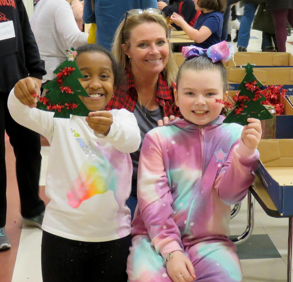 A teacher and two students, who are proudly displaying the cutouts of green Christmas trees they've decorated