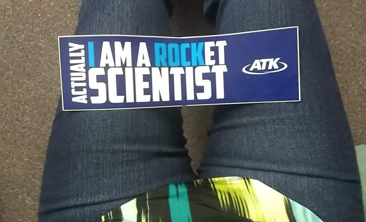Sticker lying across someones legs that says 'Actually I Am a Rocket Scientist ATK'