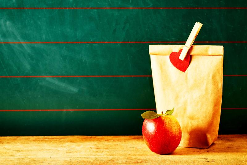 A school lunch bag and an apple on a table, against a green chalkboard
