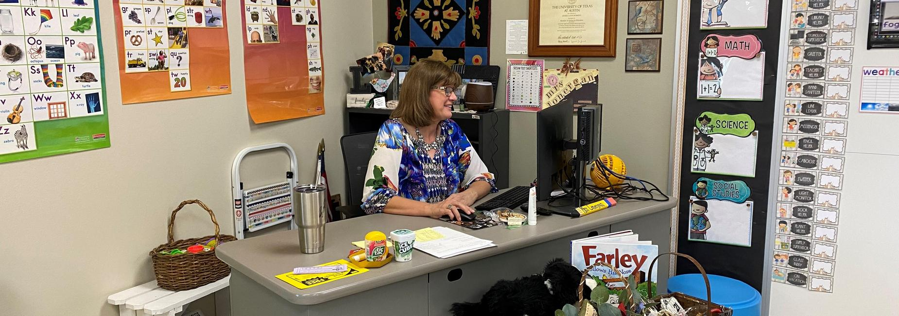 woman smiling while working at her desk on the computer