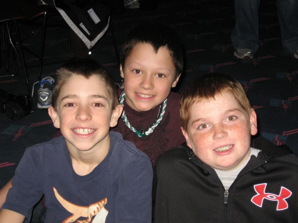 three boys smile at camera