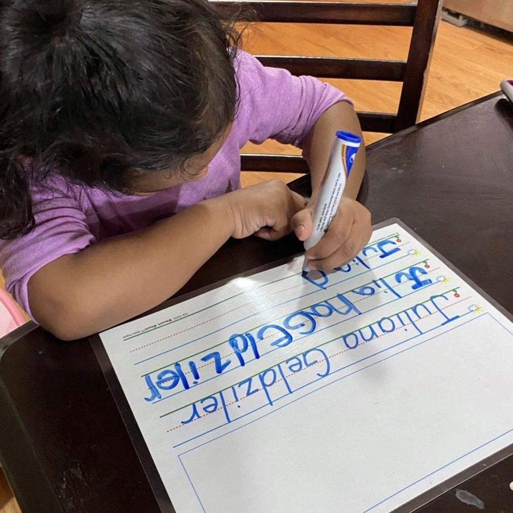 Girl practicing writing her name