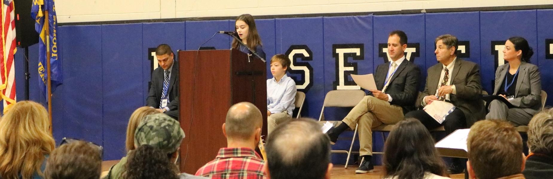 Roosevelt 7th grader Andrea Hanchuk speaks to the meaning of Veterans Day during the school's 20th Annual Veterans Day Honor Ceremony.