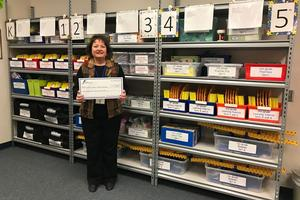 mrs young poses with the frenship foundation grant check in front of the new math manipulatives library