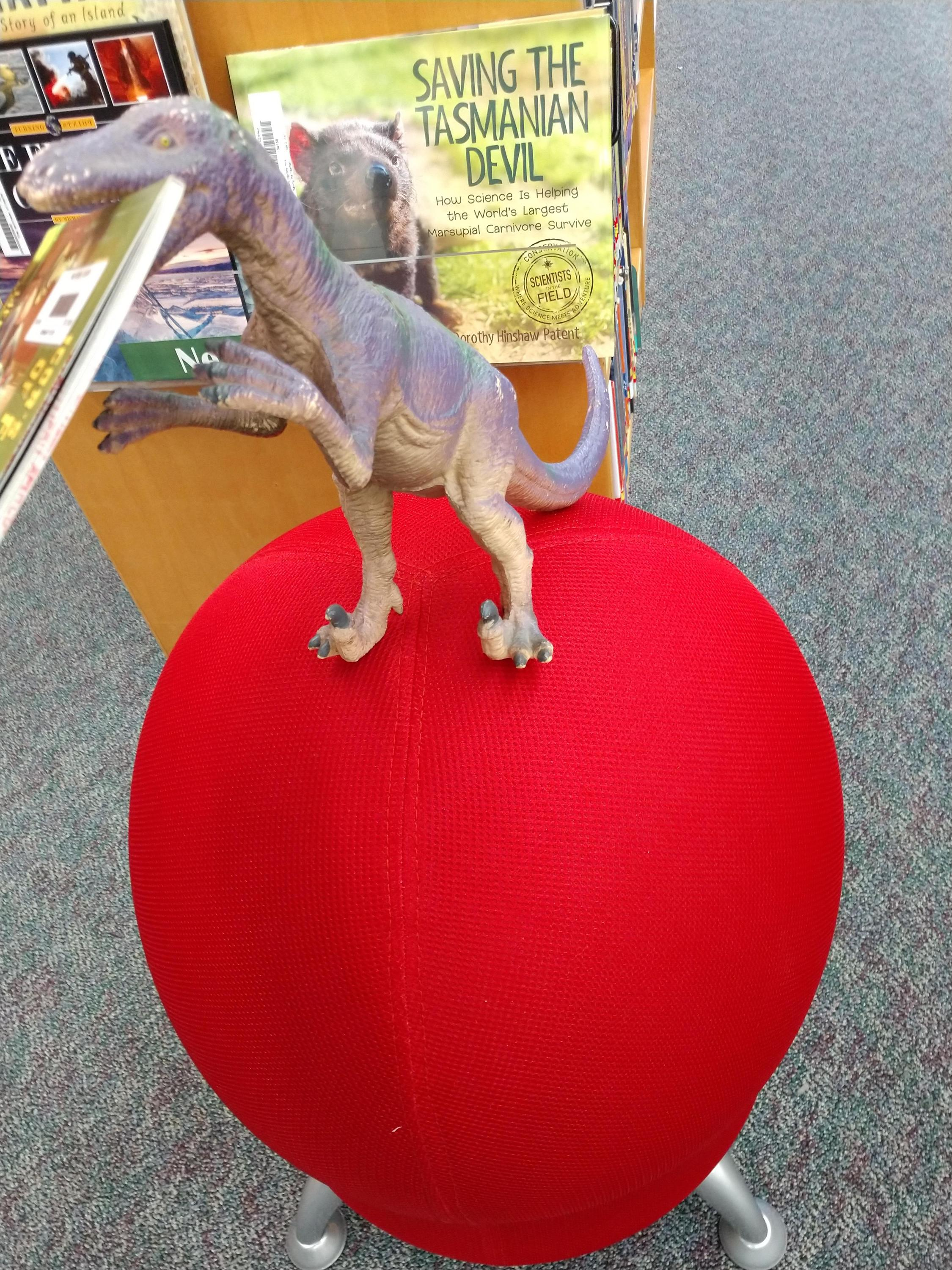 Steve the dinosaur showing off some new library furniture