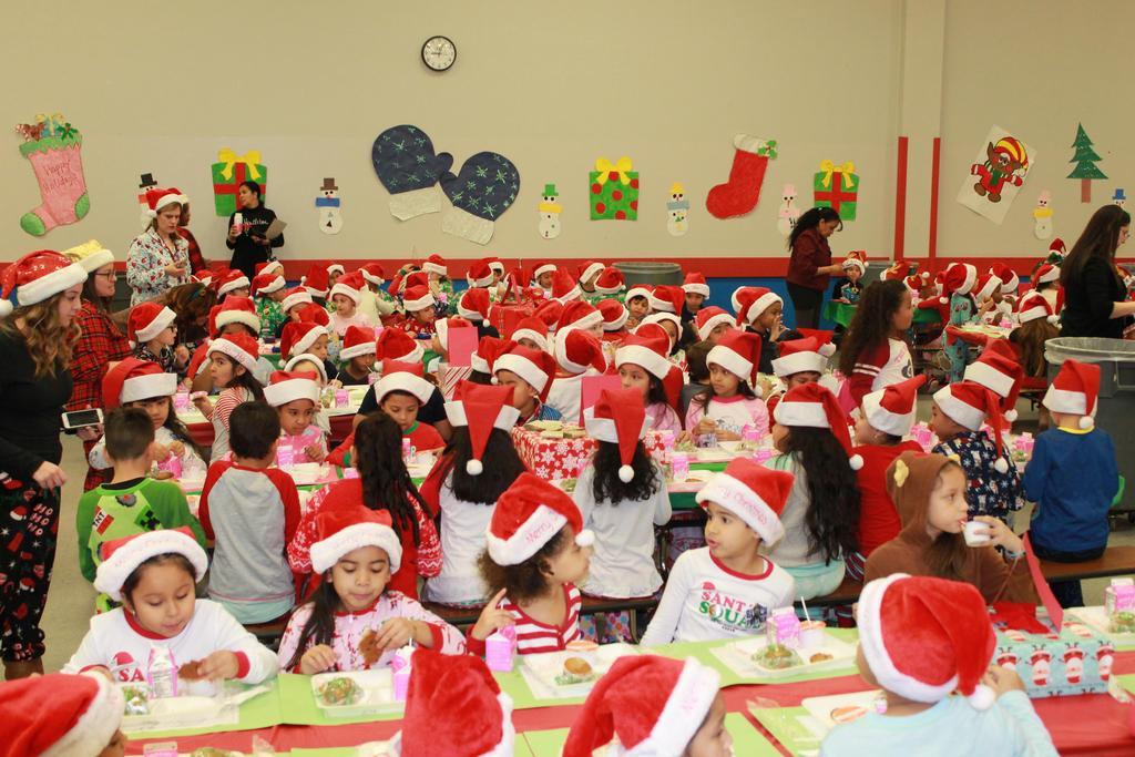 three rows of children wearing pj and santa hats enjoying breakfast