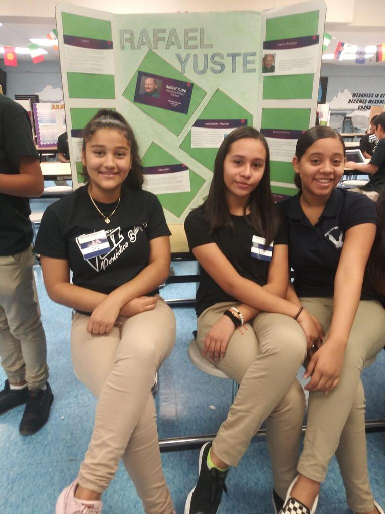 three girls seated in front of a Rafael Yuste poster board