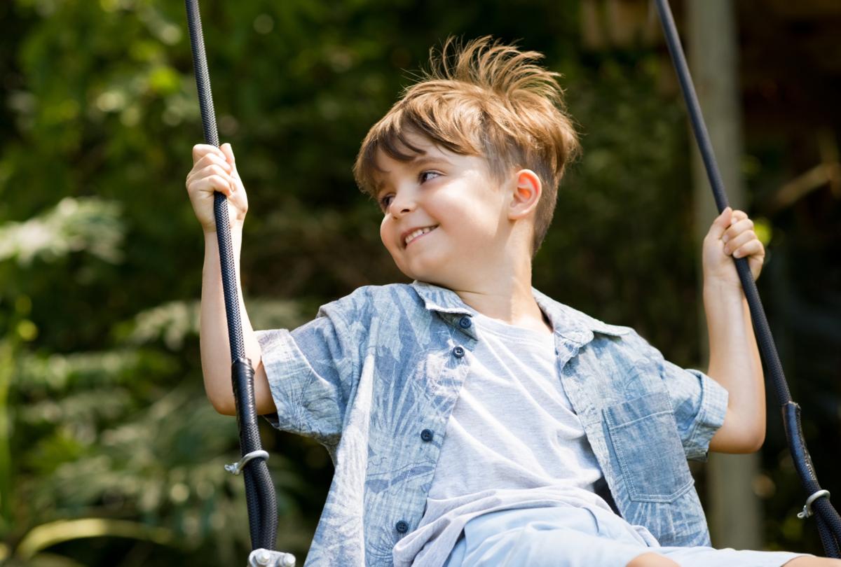 boy in jean shirt swinging in summer