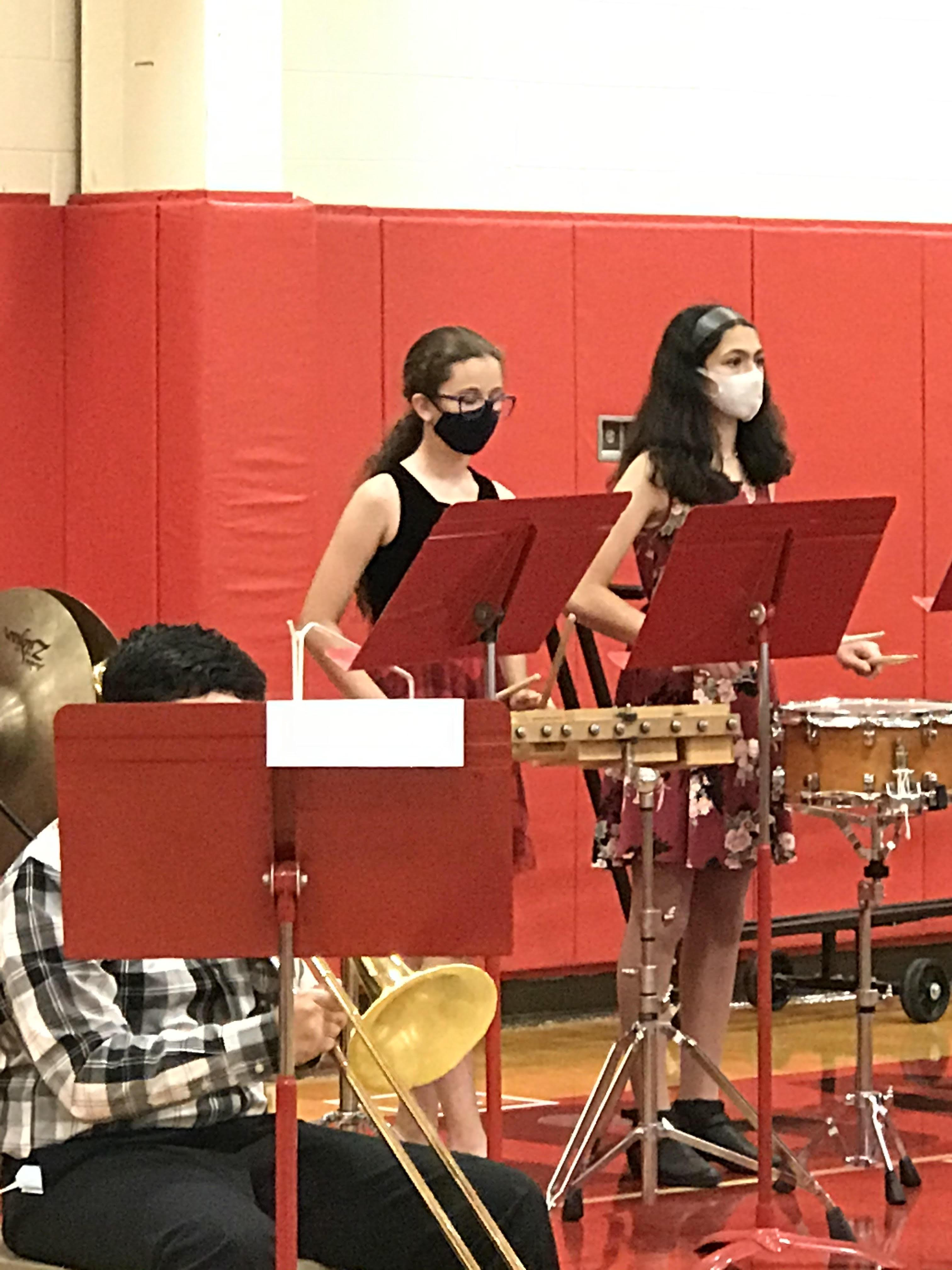 Two students playing percussion instruments in the Benjamin gym
