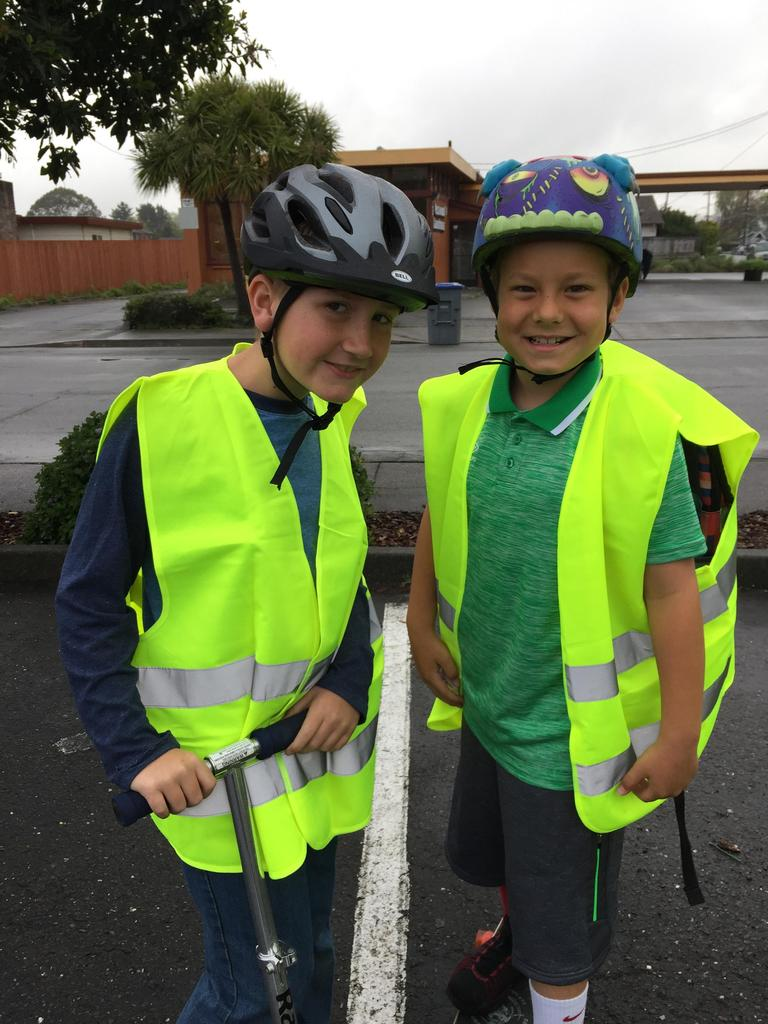 two boys smiling with scooters