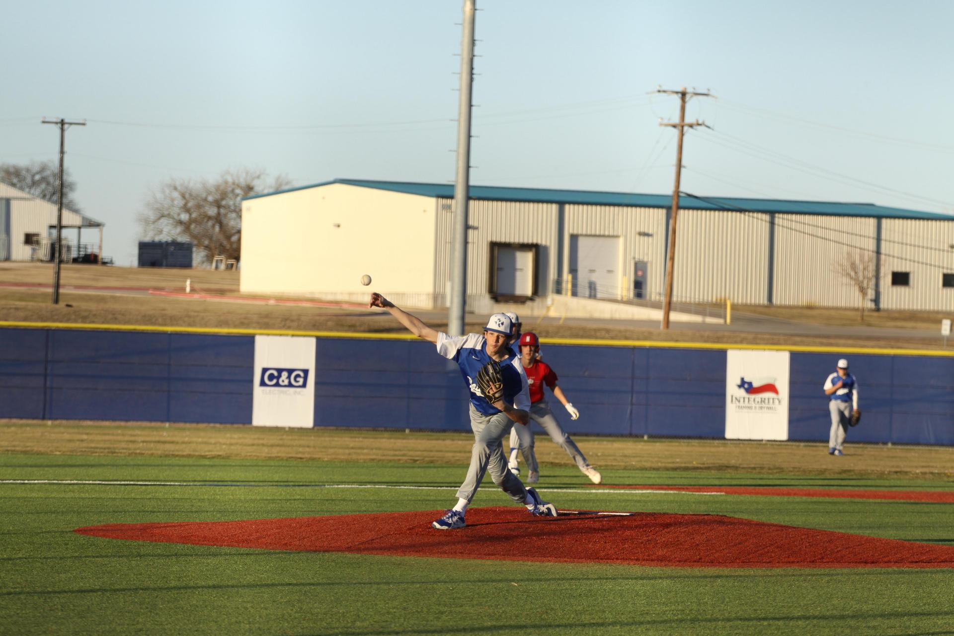a baseball player throws a pitch to the batter