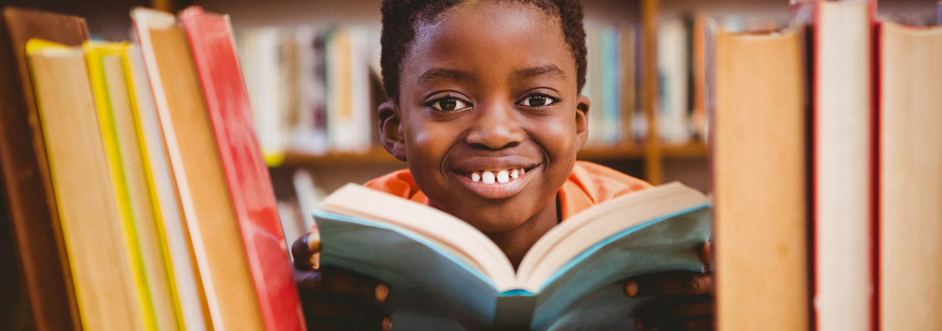 young boy surrounded by books