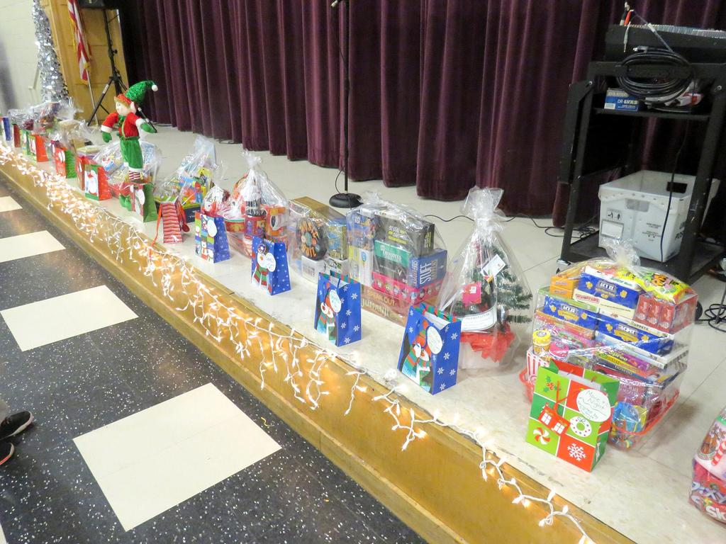 A row of elaborate gift bags are set up on the stage for the raffle
