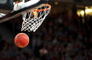 Stock image, a basketball going through a net