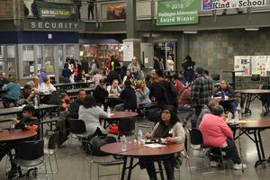 people sitting at tables at the bean feed in the High School Commons