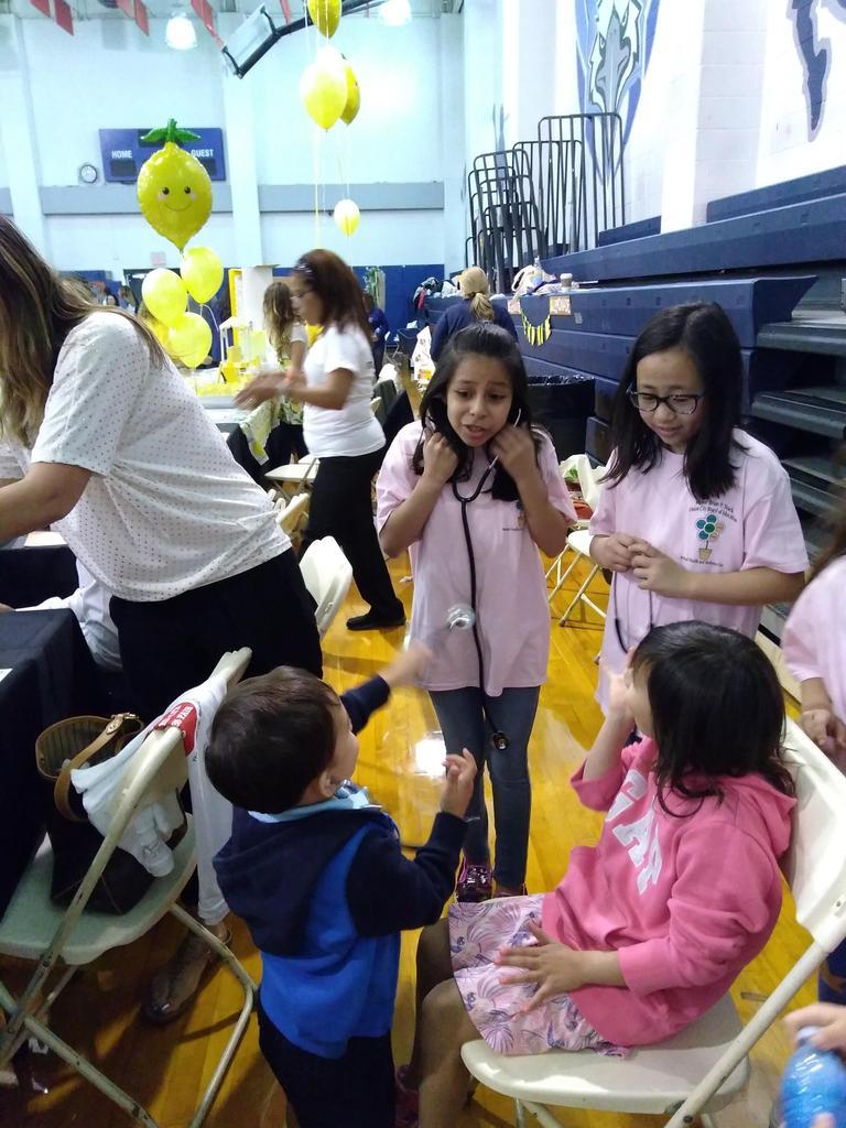 two girls using stethoscopes to listen to little kids heart beats
