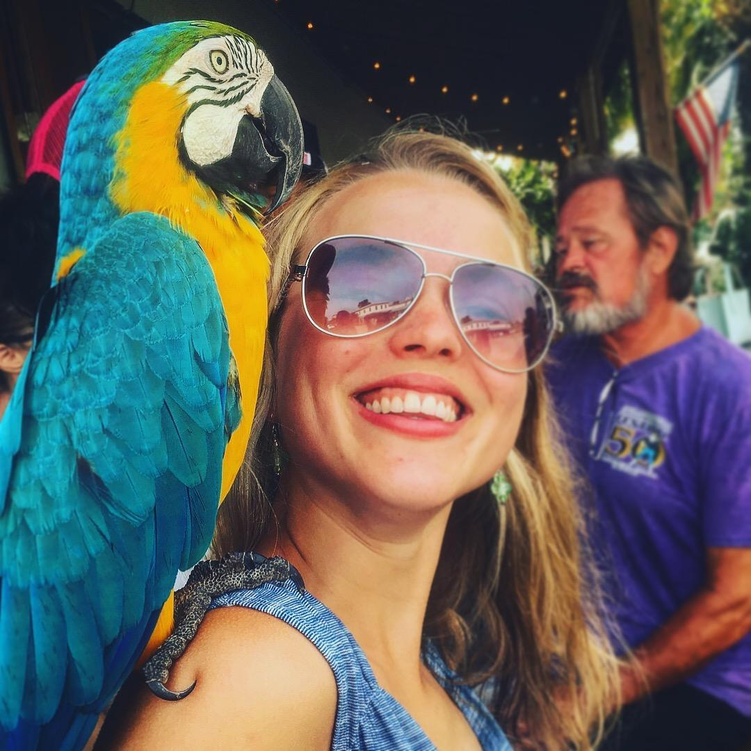 Photo of Ms. Thomson with a macaw