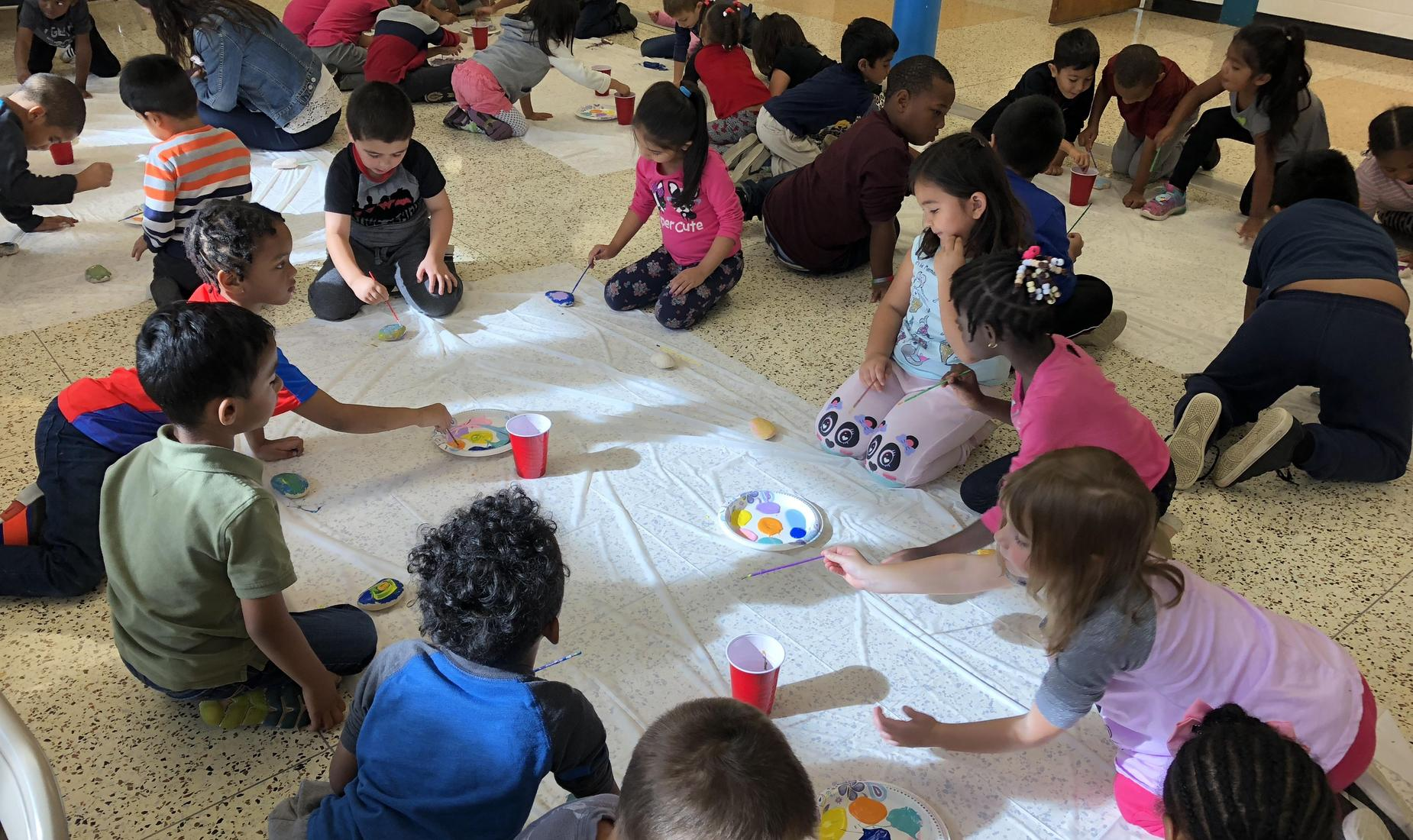 Rush students sitting on the floor painting rocks for their Rock Garden