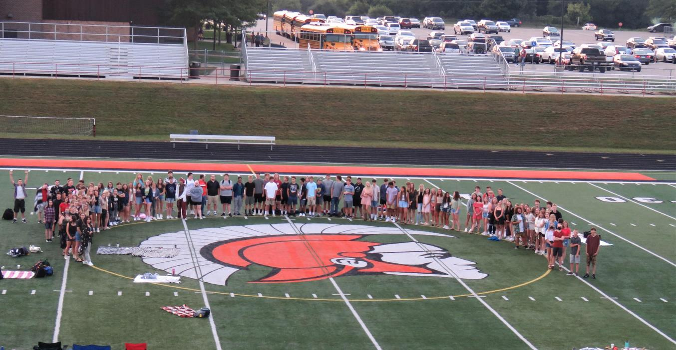 Members of the TKHS Class of 2022 gather early on the first day for a photo on the football field.