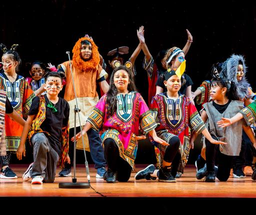 PS116K Student actors posing on stage at end of Lion King Performance