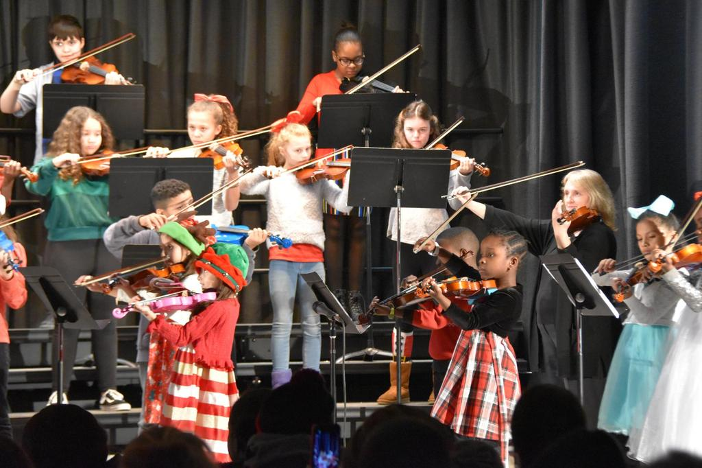 A close-up of a section of the stage of students playing violin