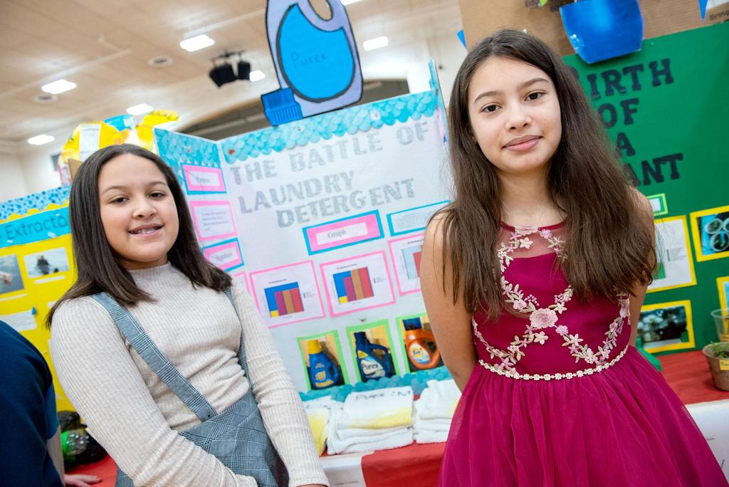 Two students stand in front of their project called The Battle of the Laundry Detergent