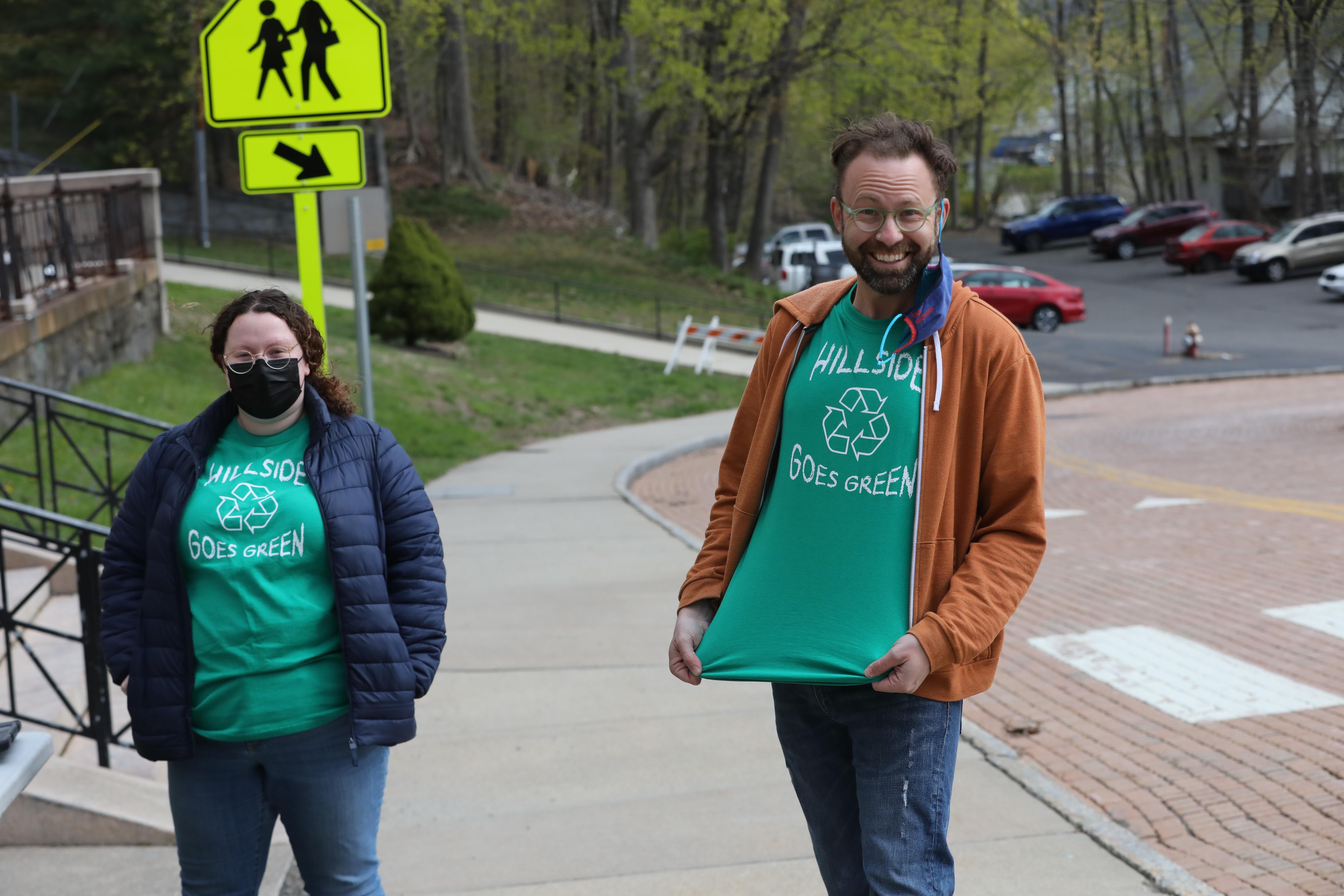 Two teachers showing off recycling shirts