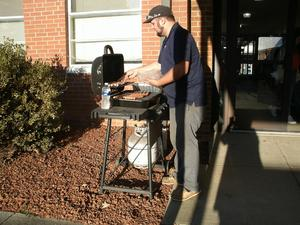 A member of the Boosters' Club grilling hot dogs.
