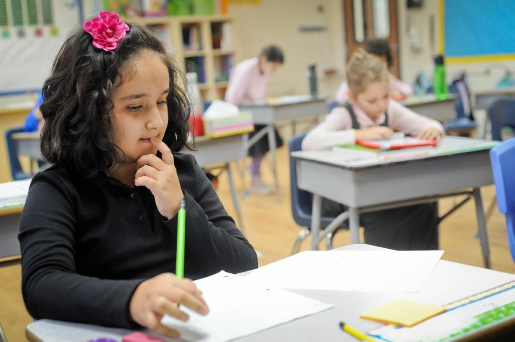 girl working on a worksheet in her classroom