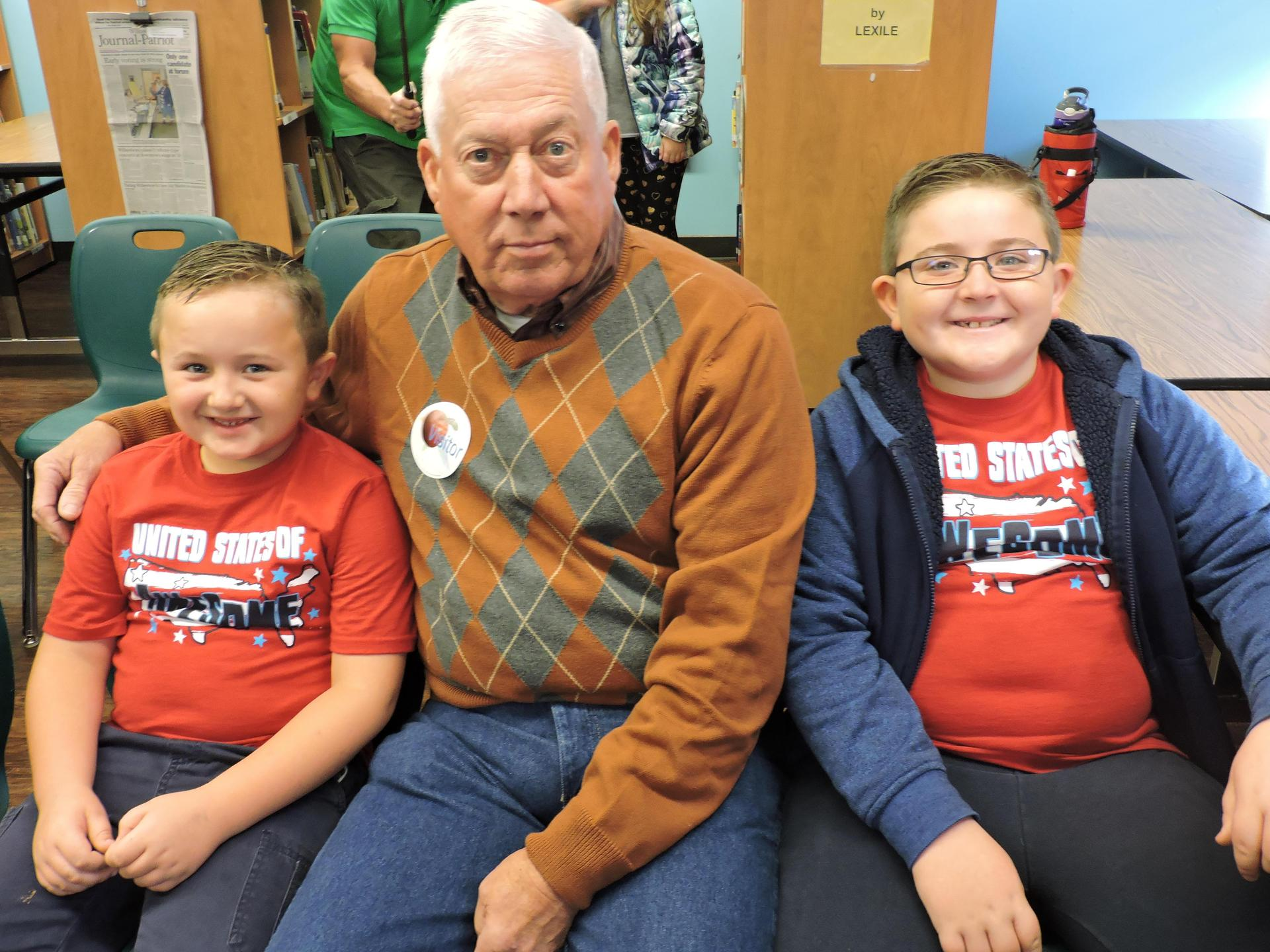 Veteran poses with two students.