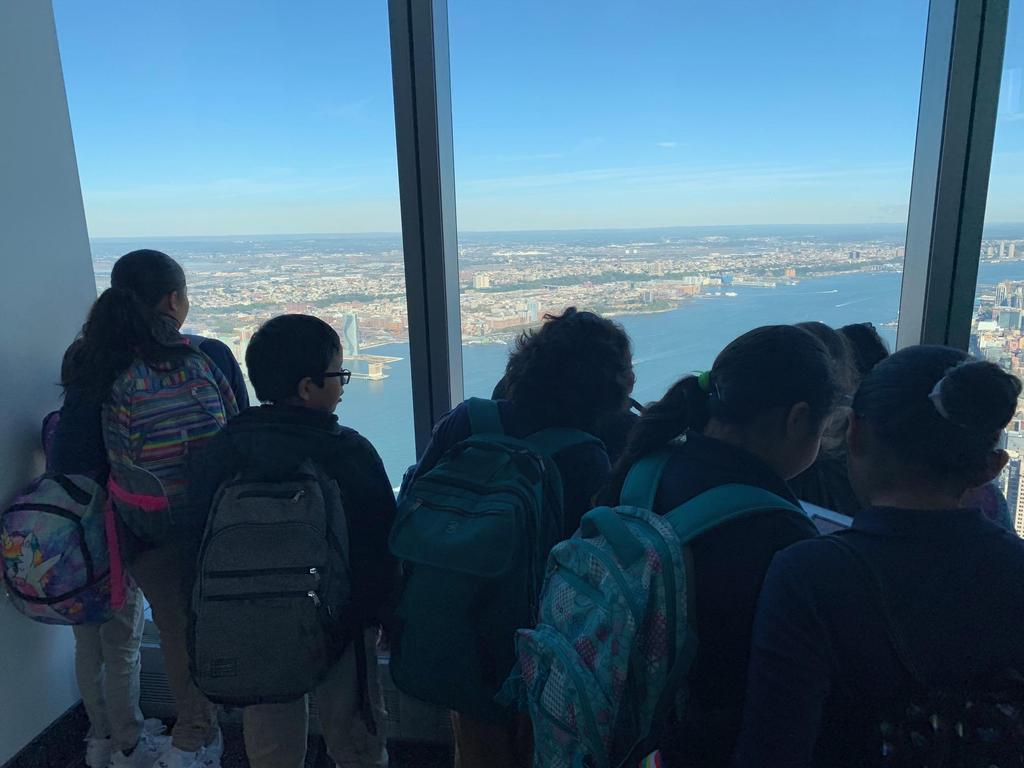 several kids taking photos with their ipads and looking out at the skyline