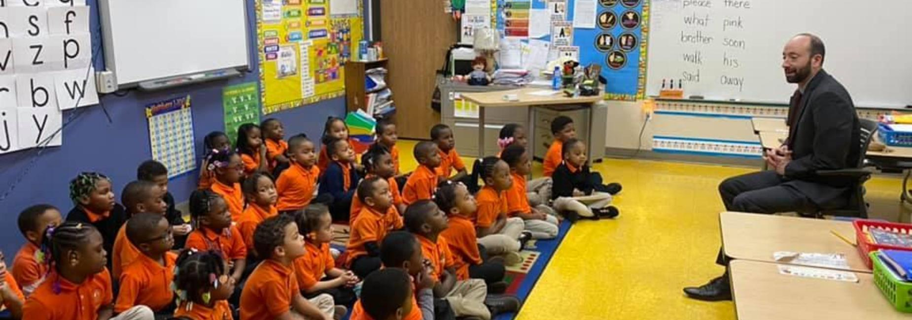 A full class of scholars in matching DIA orange polos listening to a speaker.