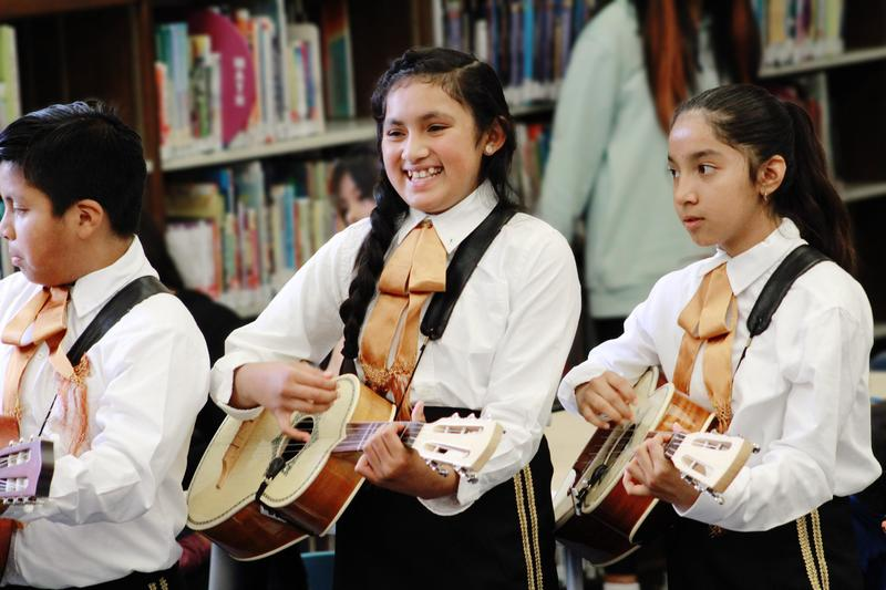 Three students playing their instruments.