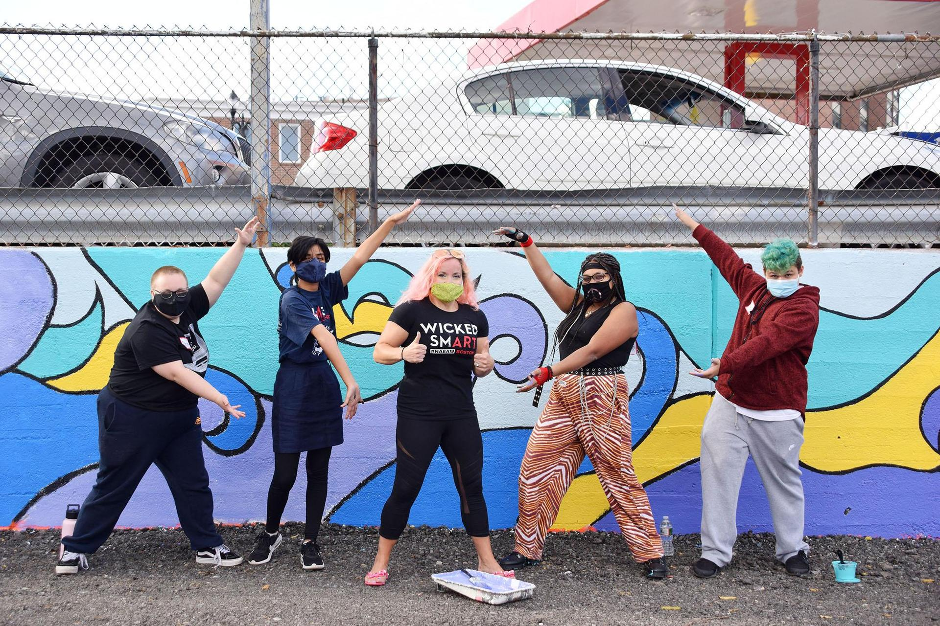 Five people, a teacher and four students, pose in front of the mural
