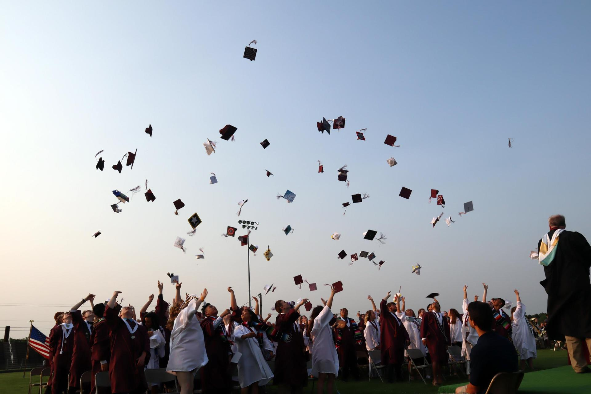 students throwing grad caps