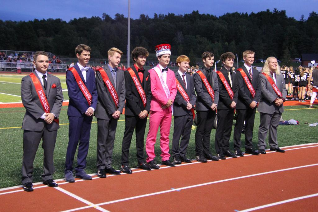 A line of males wearing suits and red sashes