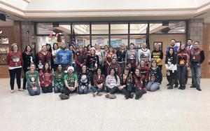 A group of teachers wearing festive sweaters
