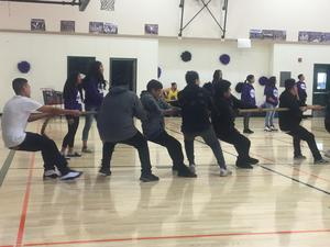 six students pulling one side of a rope in a tug-of-war