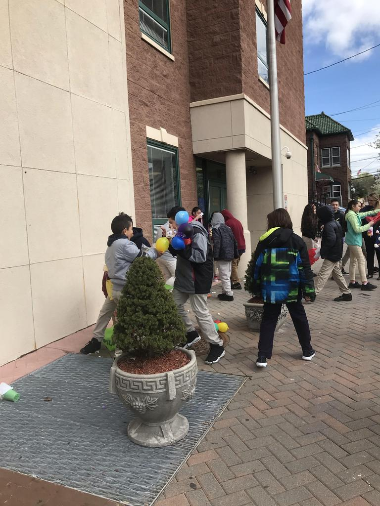 students in front of the building picking up their dropped eggs