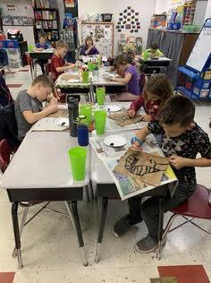Students work on painting a pharaoh on the papyrus they made
