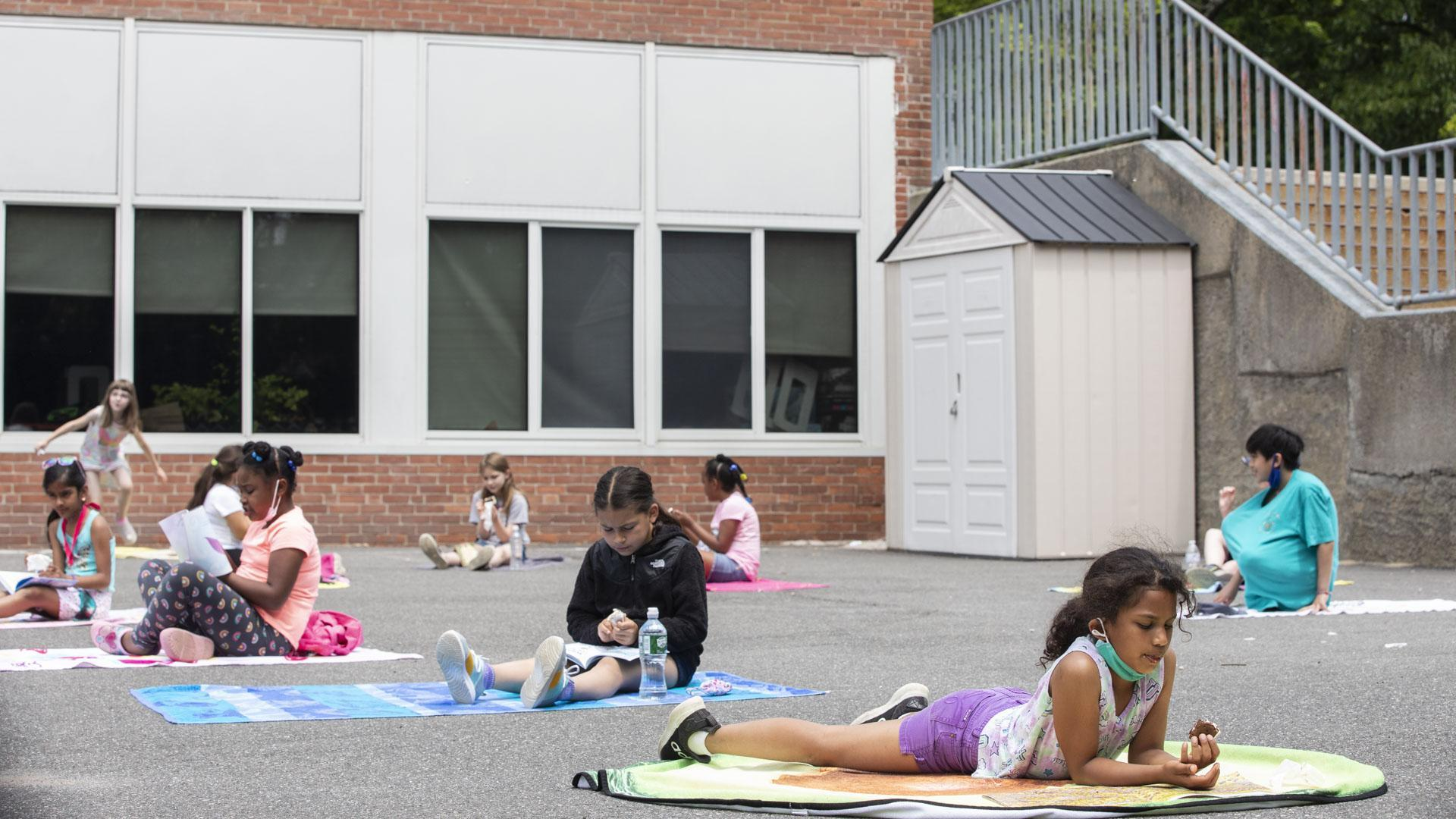 Students reading on beach towels on blacktop