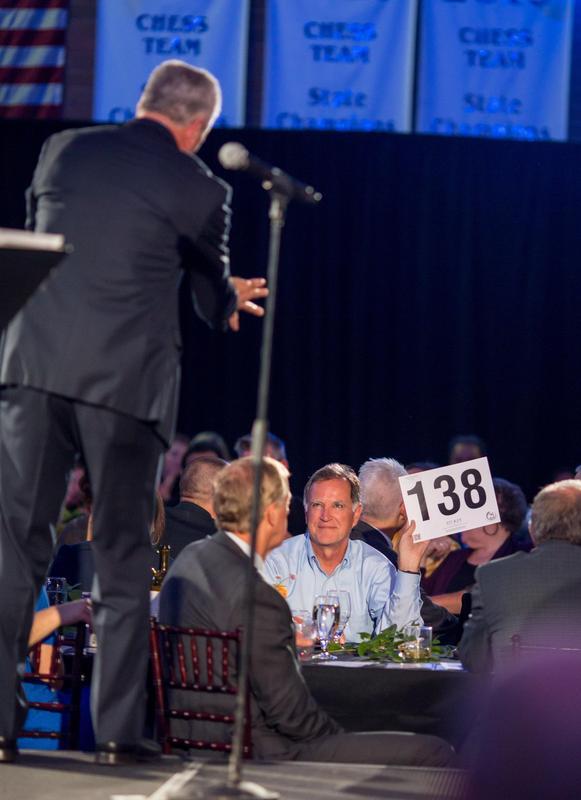 man holding bidding number