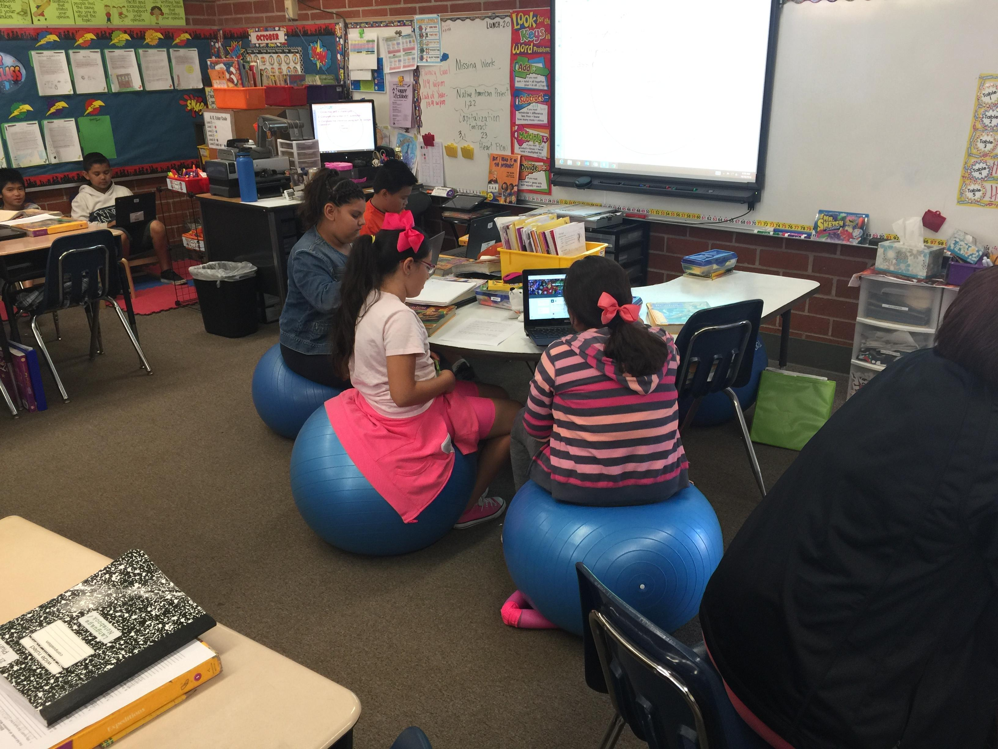 A classroom with several students doing work.  Three students in front sitting on inflatable ball chairs.