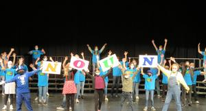 The cast and choir pose at the end of a song.