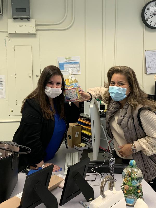 2 teachers posing with goody bag over desk
