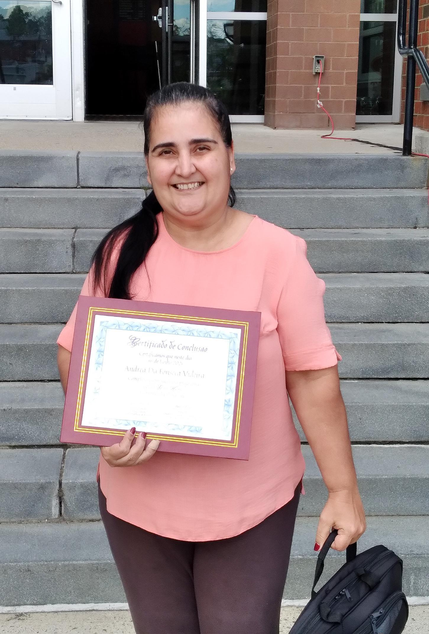 Parent holding a certificate and a case containing a Chromebook