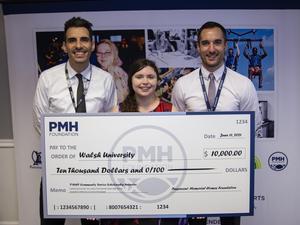 OLSH graduate Sydney K holding large scholarship check