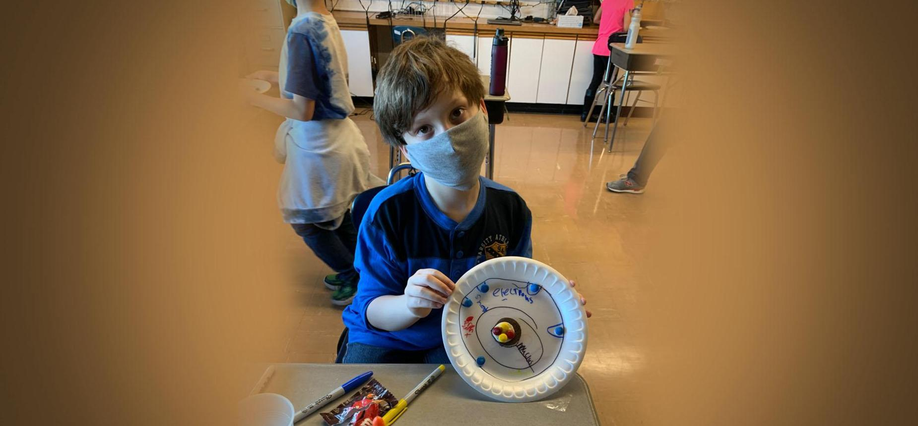 4th grade student creating atom models with food