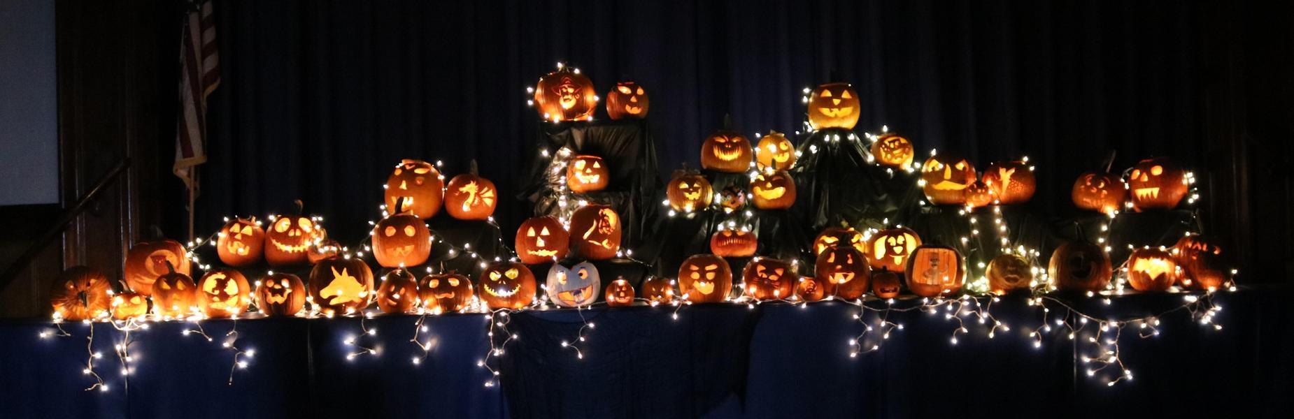 Carved pumpkins lit in the darkened gym at McKinley School on Halloween.