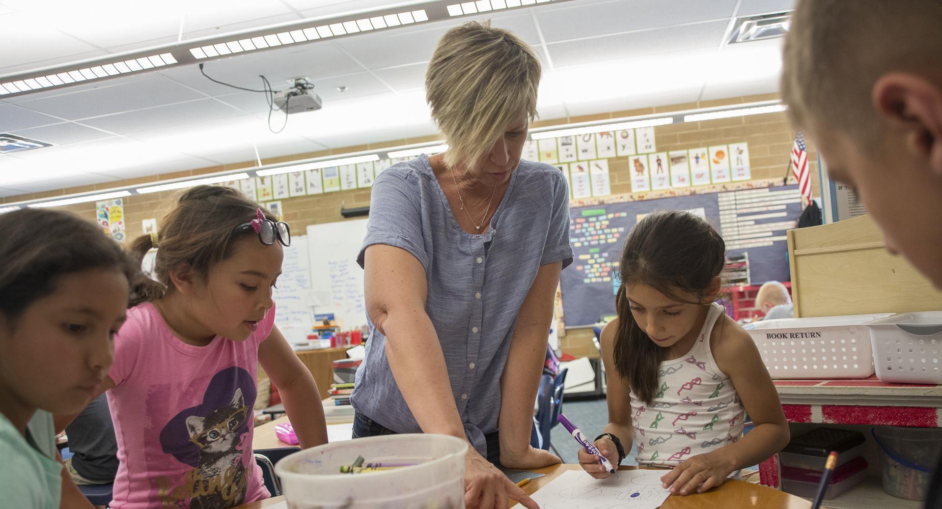 Teacher at desk helping three girls with their class work.